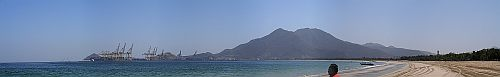 Panoramic beach scene in Khor Fakkan, with the port in the distance