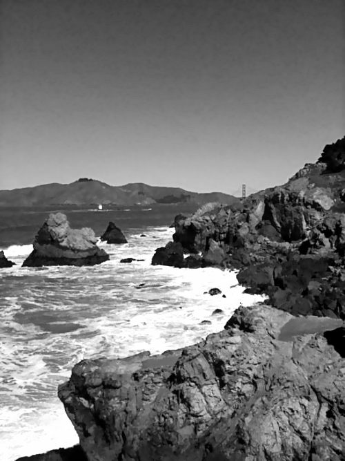 Rocky shore with Golden Gate Bridge in the distance
