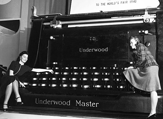 Two women lounge on a  giant typewriter at The World's Fair in 1940