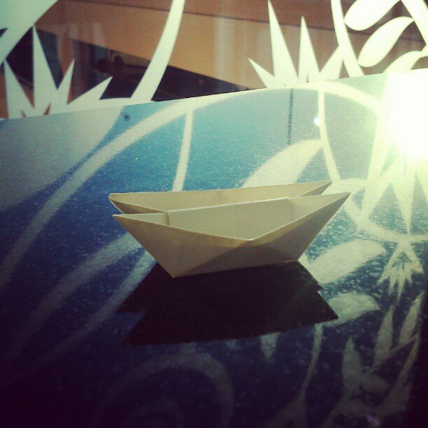 Origami double boat on a reflected pattern