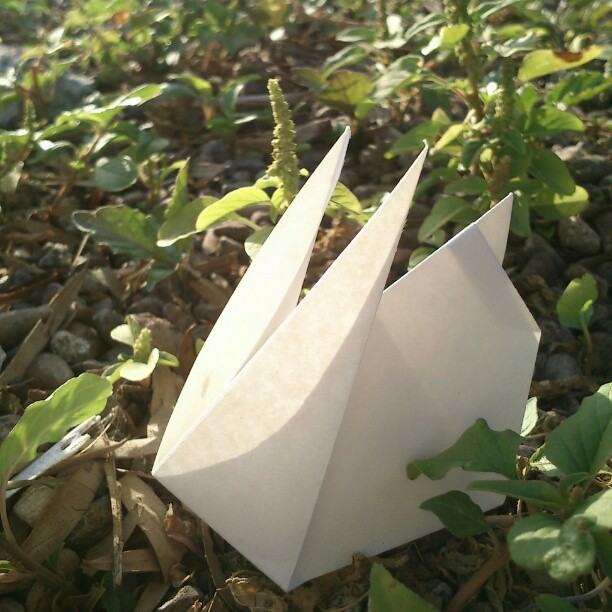 Origami rabbit among plants on the ground