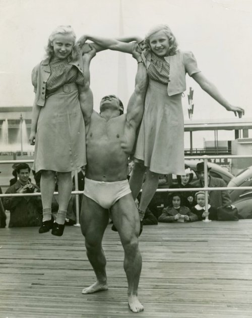 Strongman hefting two young girls