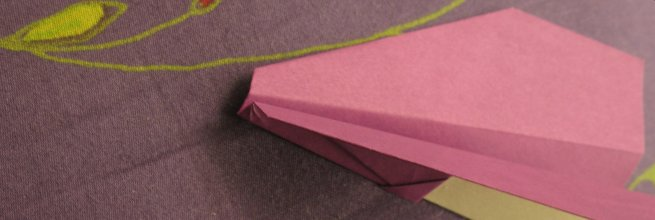 Paper plane on a patterned fabric