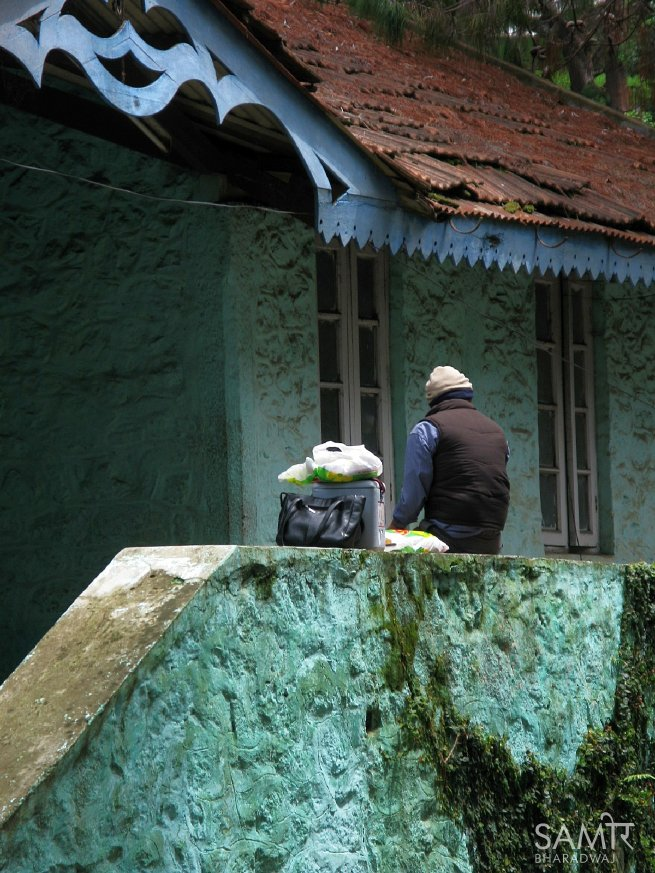 Man waits outside an old stone building with bags