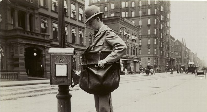 Vintage photo of a postman at a letter box