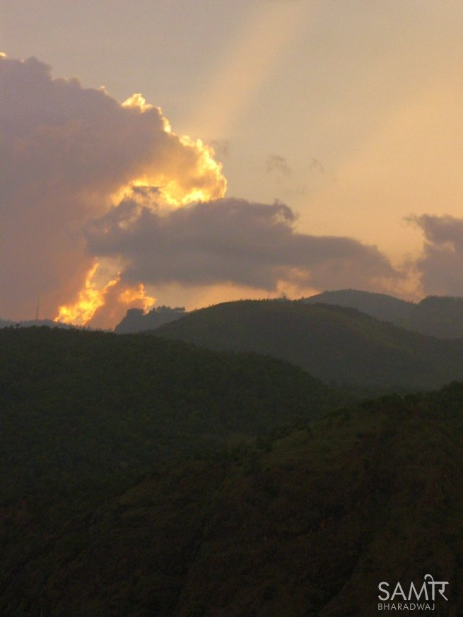 A shaft of sunlight pierces through the clouds at sunset over the Nilgiri hills