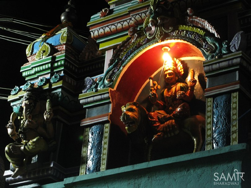 Decorative temple sculptures at night lit by street lights and an incandescent bulb